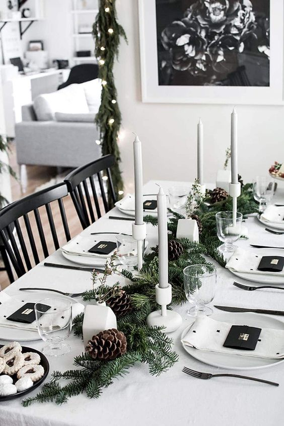 a Nordic Christmas table with a fir runner with pinecones, grey candles, white porcelain and printed napkins and cookies on a plate