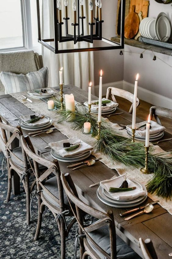 a Nordic Christmas tablescape with a white burlap runner, fir branches, candles, grey plates, bells and an upcovered wooden table and chairs