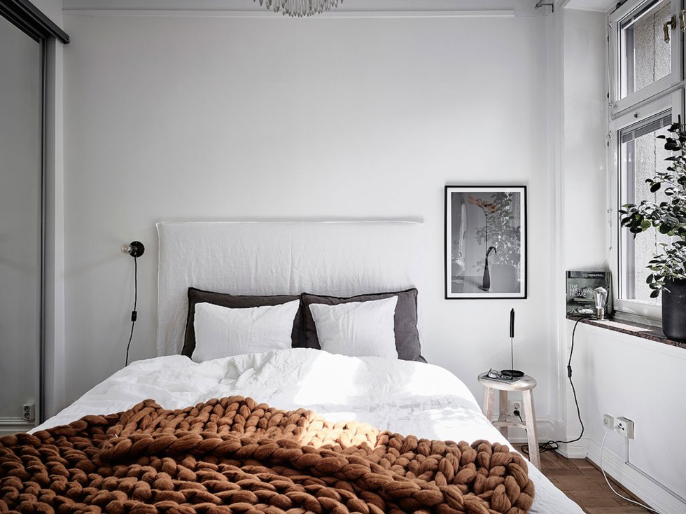 a Nordic bedroom in grey and white, a white upholstered bed, stools, sconces, an artwork and potted plants