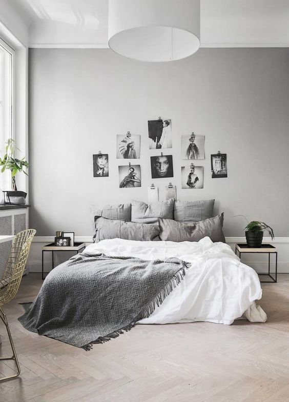 a Nordic bedroom with black and white furniture, grey and white bedding, a simple gallery wall, a desk and a metal chair