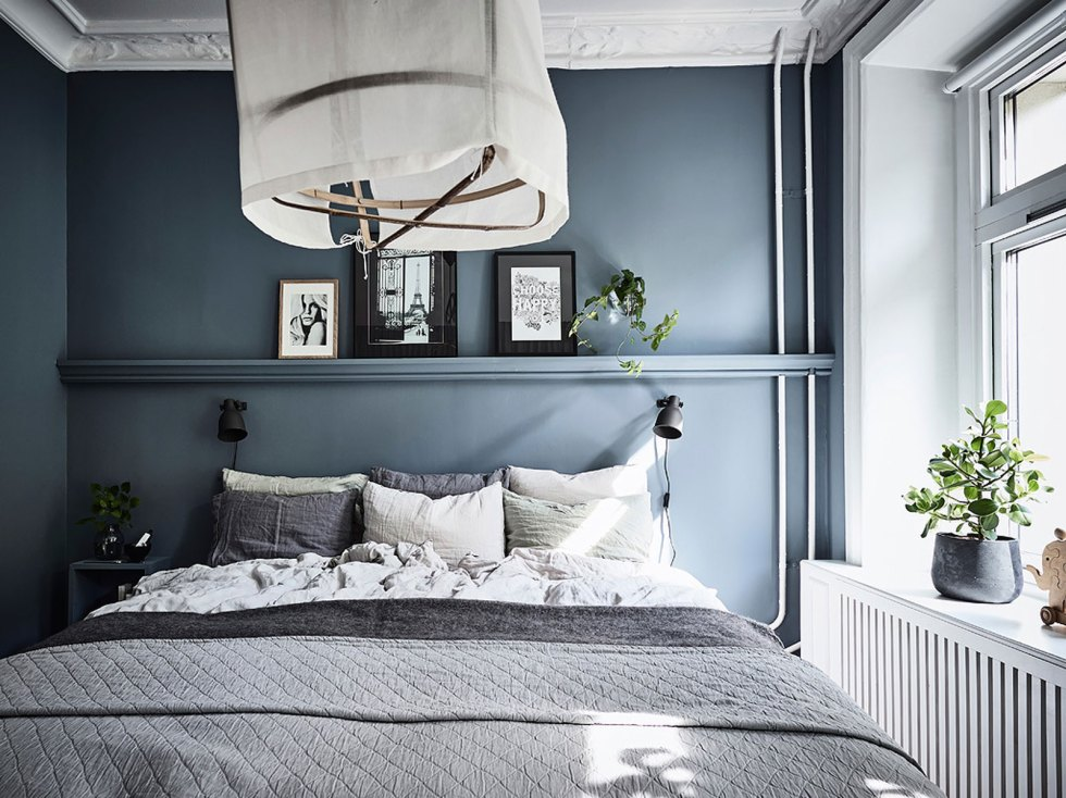 a Nordic bedroom with blue walls, stucco on the ceiling, wall-mounted nightstands and a cool bed, a ledge with artworks