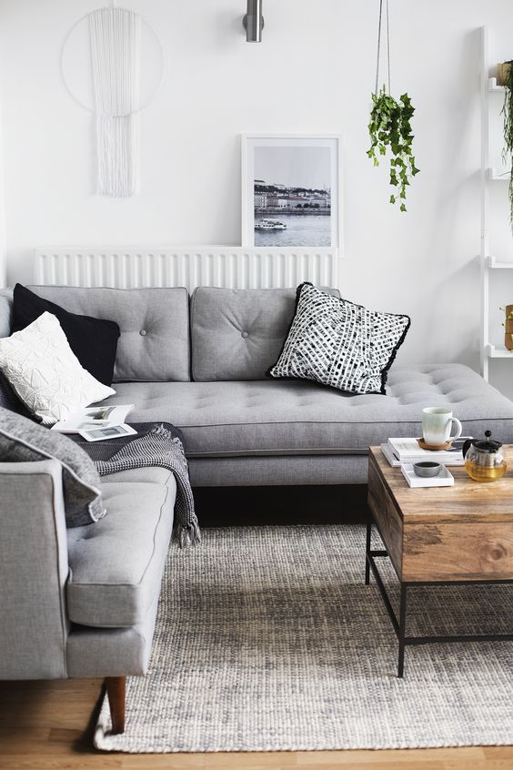 a Nordic living room with a grey sectional, monochromatic pillows, a macrame on the wall, potted greenery and a wooden table