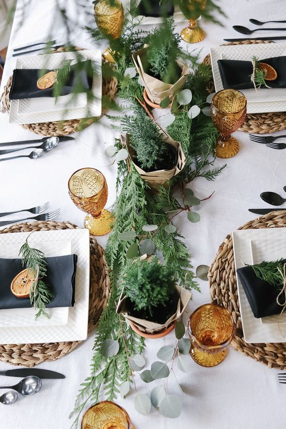 a Scandinavian Christmas tablescape with woven chargers, colored glasses, a greenery and foliage runner, black napkins and dried citrus
