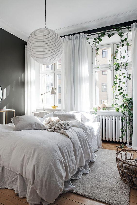 a Scandinavian bedroom with a black wall, a bed with cozy linen bedding, a paper lamp, a vine and a basket with towels