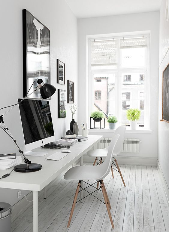 a Scandinavian home office with a shared desk, chairs, a black and white gallery wall and potted greenery is very chic