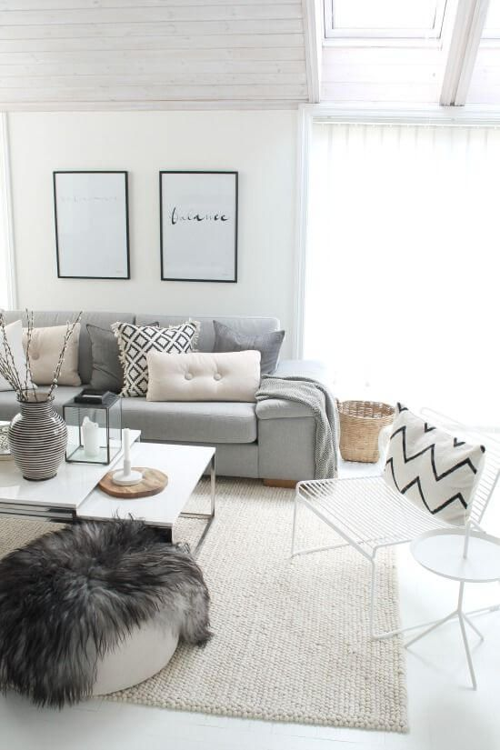 a Scandinavian living room with a grey sofa, a white chair and a table, a pouf, a couple of tables and printed pillows