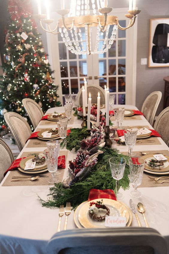 a beautiful Christmas tablescape with burlap placemats, fir branches with berries and pinecones, candles, gold cutlery and chargers