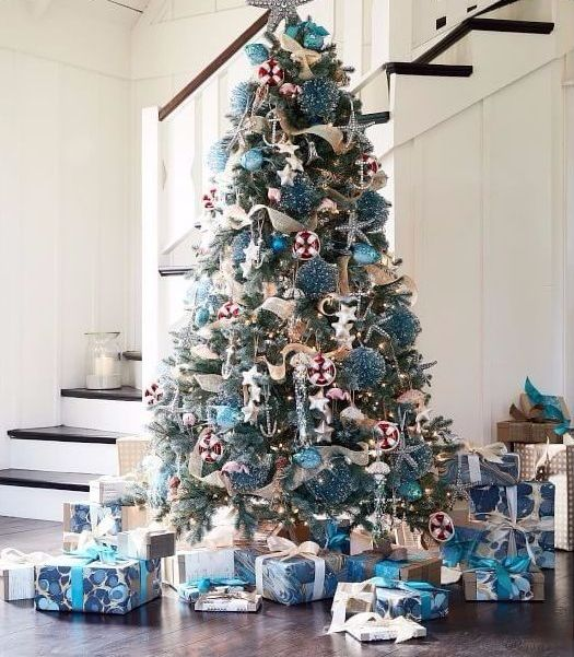 a beautiful Christmas tree with stars, blue glitter and light blue ornaments plus a star topper for beach Christmas