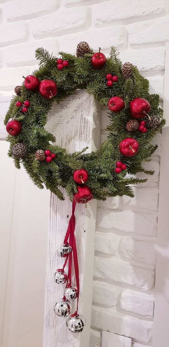 a beautiful Christmas wreath of fir, red berrries, apples, pinecones and silver bells hanging on red ribbons is lovely