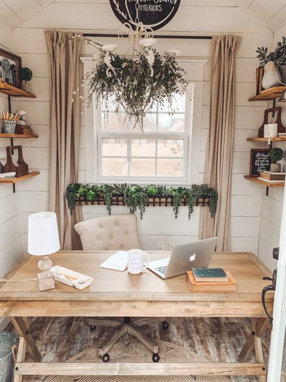 a beautiful farmhouse home office with a wooden desk, open shelves, a leather chair and lots of greenery for coziness