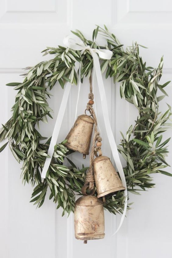a beautiful greenery Christmas wreath with oversized vintage bells and a white ribbon bow on top is a lovely vintage decoration