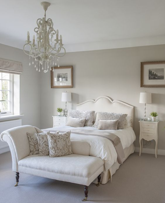 a beautiful neutral vintage bedroom with an upholstered bed and bench, a chic crystal chandelier and some comfy textiles is lovely