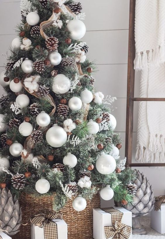 a beautiful rustic Christmas tree decorated with snowy pinecones, oversized white ornaments, vintage bells and burlap ribbons