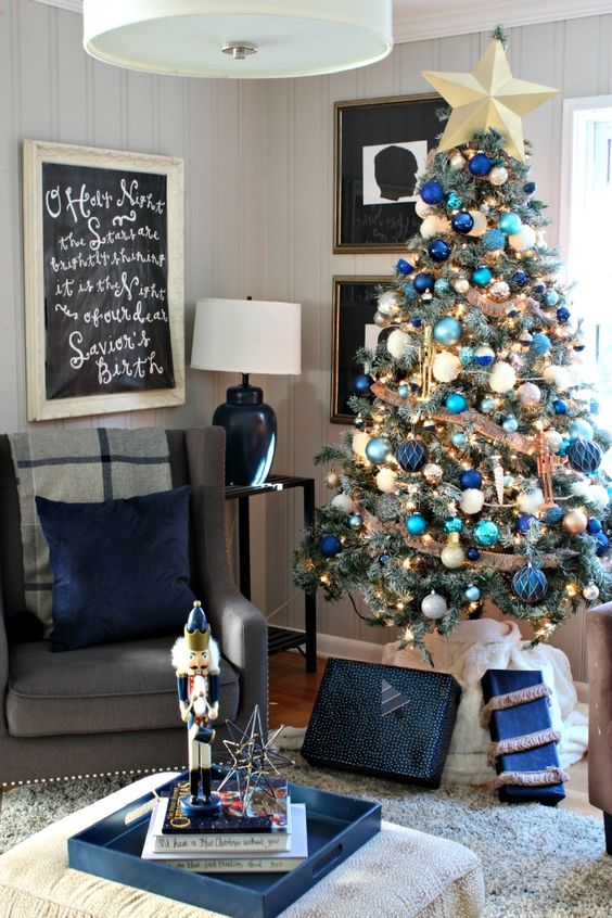 a bold Christmas tree with navy, green, blue and turquoise ornaments, burlap ribbons and a gold star topper