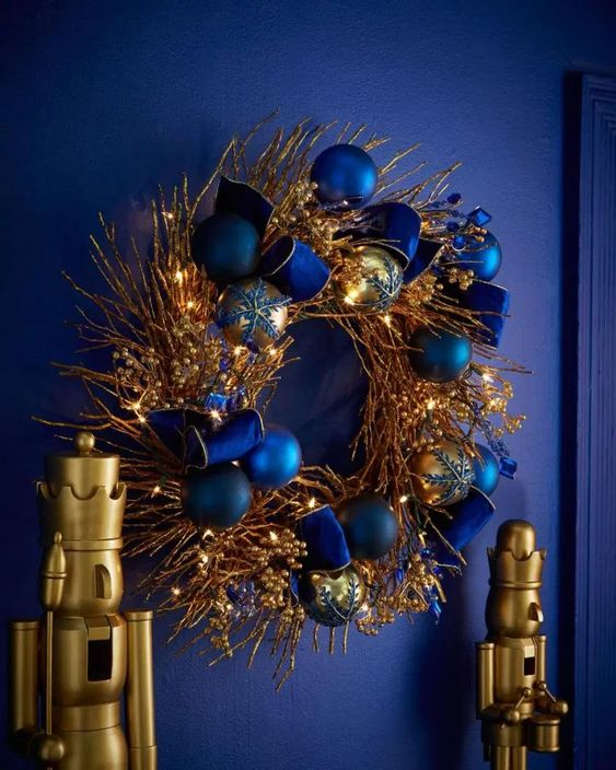 a bold Christmas wreath with gilded branches and twigs, lights and navy and blue ornaments is a bold statement