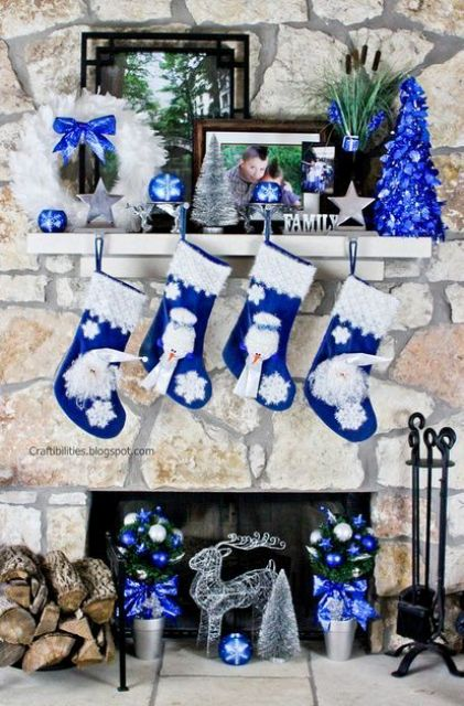a bold blue Christmas mantel with an electirc blue Christmas tree, a white feather wreath with a blue bow, blue and white stockings and ornaments