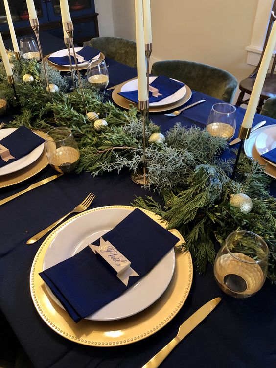 a bold modern Christmas tablescape with gold chargers and cutlery, ornaments and candleholders, navy linens is wow