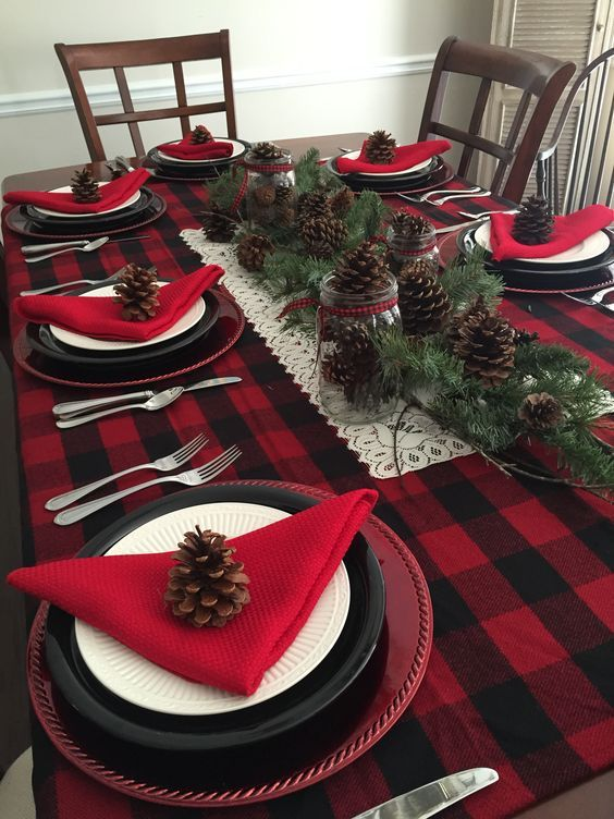 a bold rustic Christmas tablescape with a plaid tablecloth, red napkins, black and white plates, pinecones and evergreens