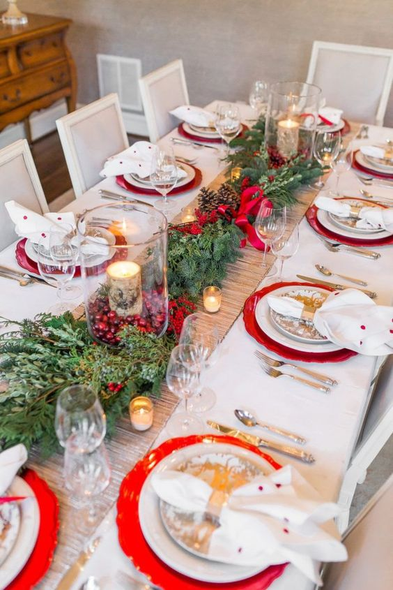 a bold rustic Christmas tablescape with a shiny runner, greenery, berries, red bows, candles and red chargers plus polka dot napkins