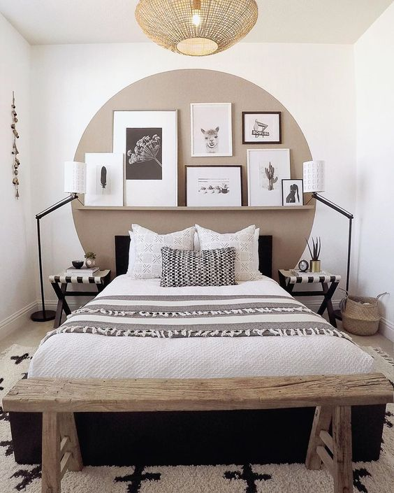 a bold small bedroom with a taupe circle on the wall, an upholstered bed, a bench, floor lamps and striped stools