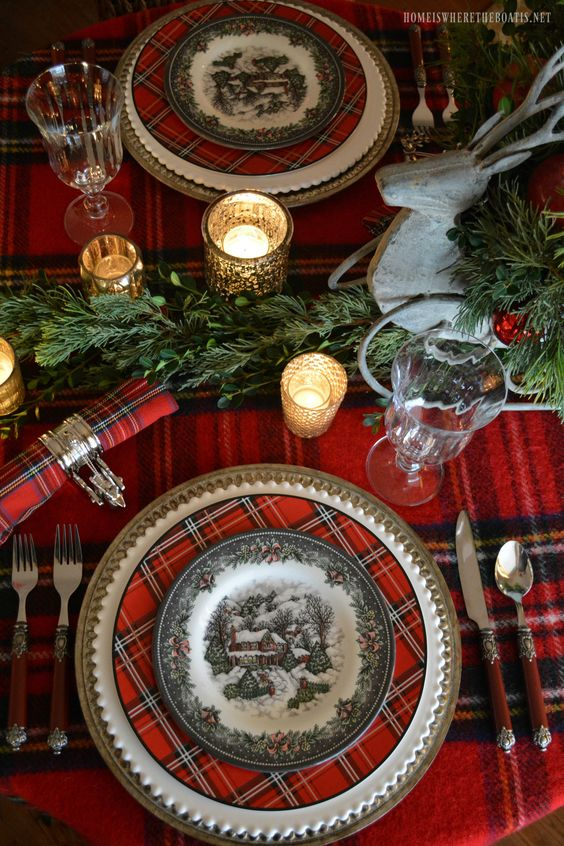 a bold traditional Christmas tablescape with a plaid tablecloth, chargers and napkins, greenery garlands, candles and chic burgundy cutlery