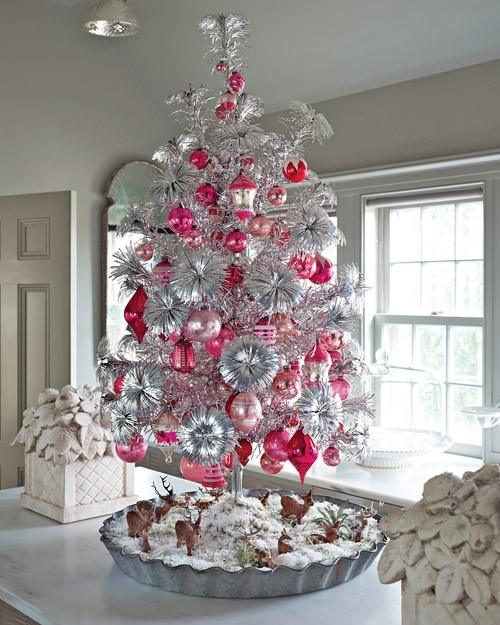 a bold vintage silver Christmas tree with pink and red ornaments and deer figurines under the tree is a catchy idea