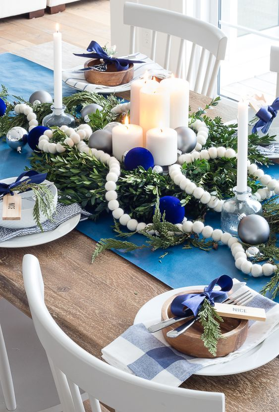 a bold white and navy Christmas tablescape with a blue runner, navy bows and ornaments, candles, beads, wooden plates and plaid napkins
