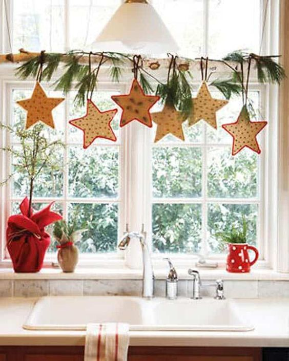 a branch with fir twigs and hanging bright stars is a cozy idea with a strong rustic feel, it will be great not only for kitchens