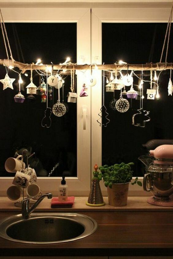 a branch with whimsical ornaments, lights and cookie cutters will make your kitchen look very cool