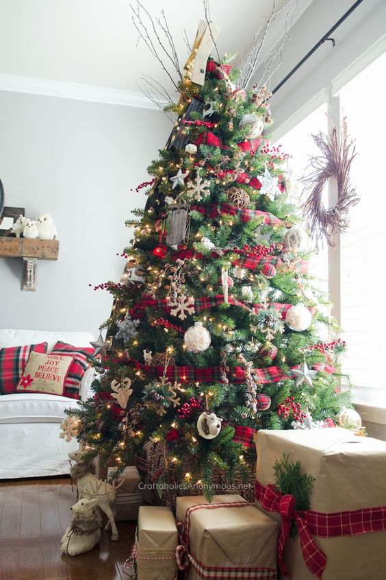 a bright Christmas tree decorated with plaid ribbons and ornaments, lights, snowflakes, deer and twigs is very cool
