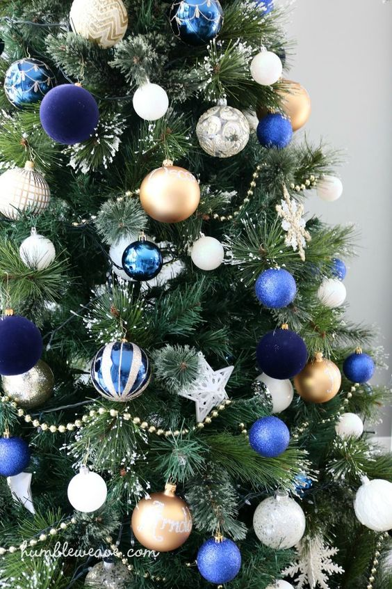 a bright Christmas tree with white, gold, blue and navu ornaments and white snowflakes is amazing and bold