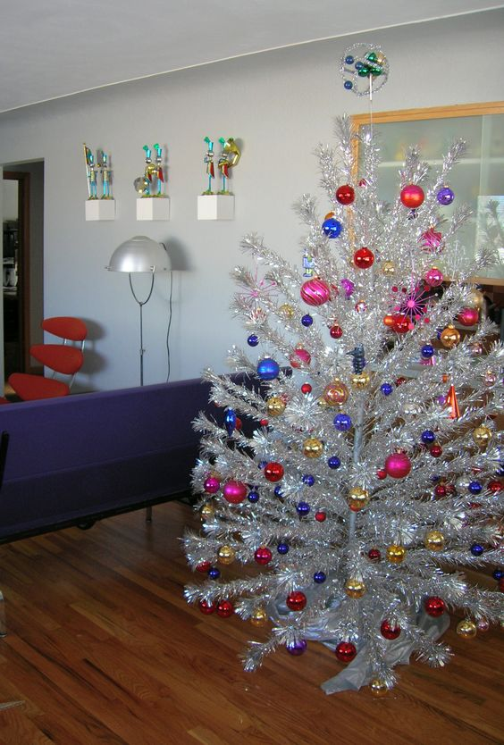 a bright and shiny Christmas tree with super colorful ornaments is a perfect idea for a mid-century modern space and it looks very catchy