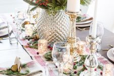 a bright farmhouse Christmas table with a striped runner, gold candleholders and bells, a mercury glass vase with berries, candles and white porcelain