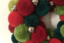 a bright red and green pompom Christmas wreath with little bells is a bold holiday decoration you can make yourself