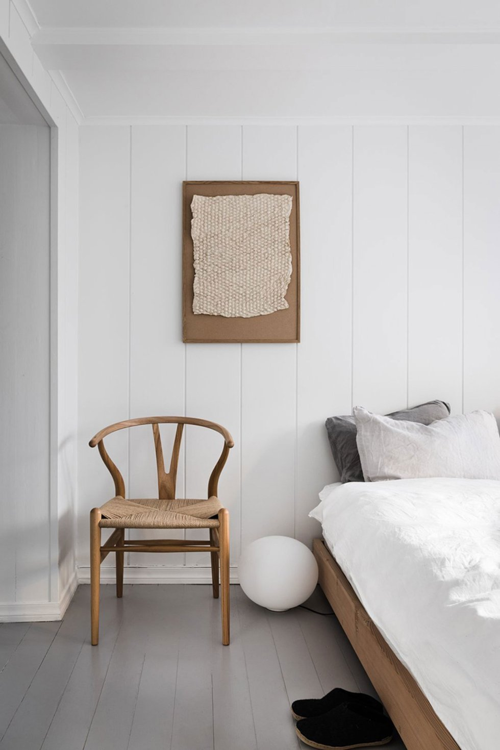 a calm and minimal Scandinavian bedroom with white walls and a grey floor, light wooden furniture, a wall art with texture and neutral bedding