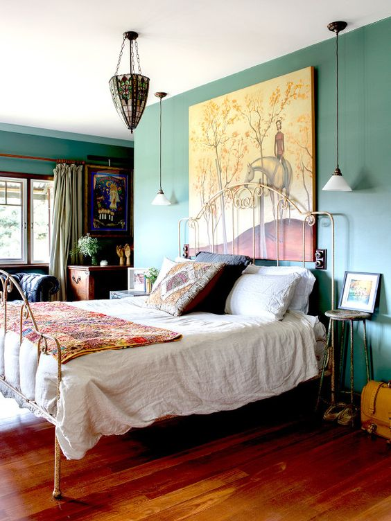 a catchy bedroom with green wall, a metal bed, a bright chandelier, printed textiles and bold artworks is a unique space