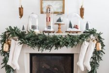 a chic Christmas mantel with a fir garland, white stockings, shiny gold bells, cloches with tinsel trees and gift boxes is amazing