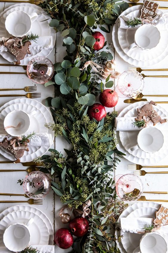 a chic Christmas tablescape with a greenery and pomegranate table runner, pink glasses, porcelain and gingerbread cookies as cards