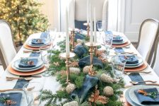 a chic Christmas tablescape with gold chargers and cutlery, blue plates and napkins, fir branches, glitter pinecones and candles