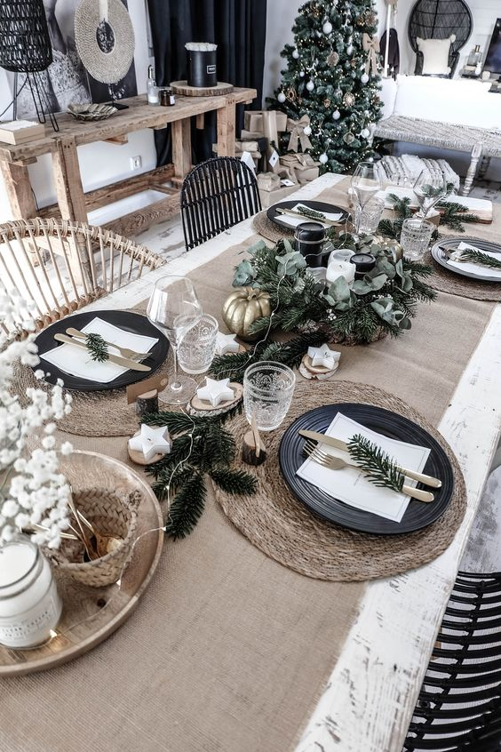 a chic Nordic Christmas tablescape with a burlap runner, woven chargers, black plates, fir branches, greenery, black and white candles, star candles and baby's breath