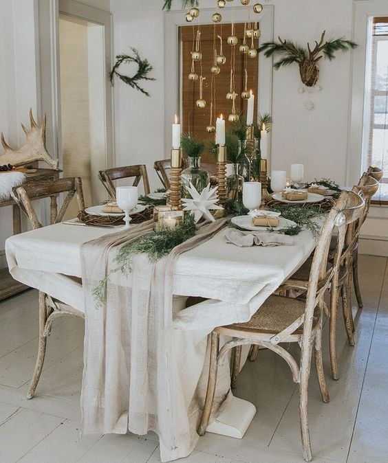 a chic Scandinavian Christmas table with gilded candleholders and lanterns, a neutral runner, greenery, gold bells over the table is amazing
