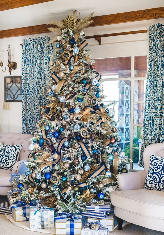 a chic and bold Christmas tree with beads, burlap ribbons, light and bold blue ornaments and a gold glitter topper