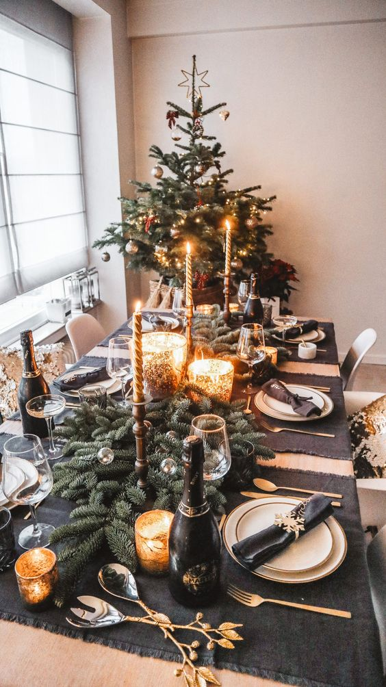 a chic and glam Christmas tablescape with black placemats, fir branches, gold candles, black napkins is very elegant