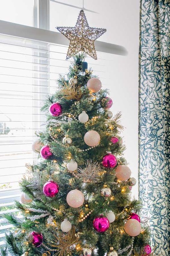 a chic and glam Christmas tree with lights, pink, white and silver ornaments and a vine star on top looks just amazing and very shiny