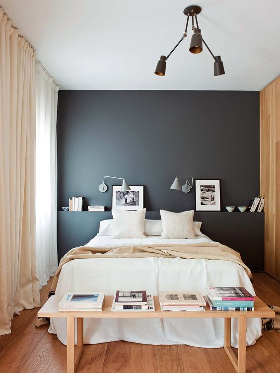 a chic small bedroom with a black accent wall, a black chandelier, neutral bedding, a wooden bench and blush curtains