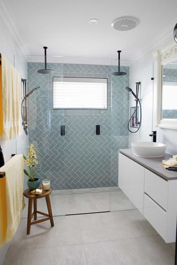 a chic tiny bathroom with light blue tiles, a floating white vanity with a cocnrete countertop, black fixtures and bold linens