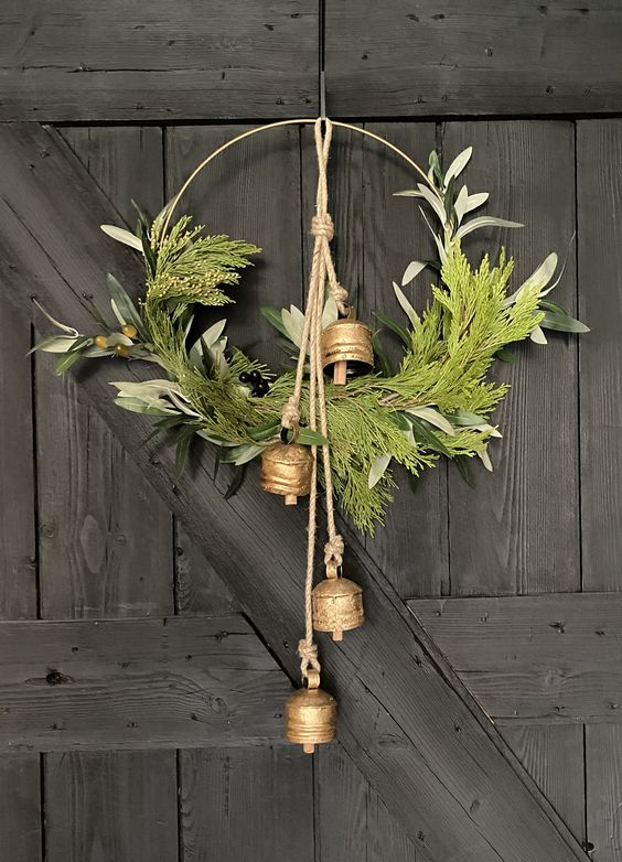 a chic vintage Christmas wreath with greenery, foliage, berries and vintage bells on rope is a very cool decoration