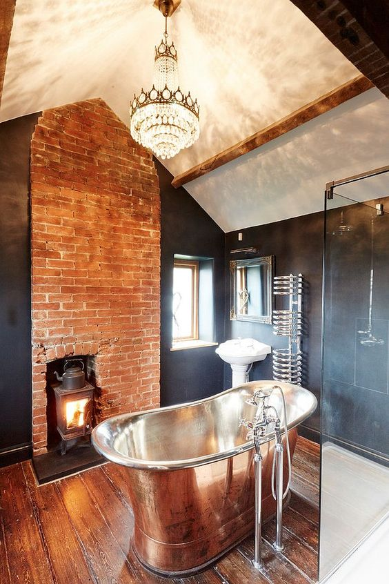 a chic vintage bathroom with a hearth in a brick wall, a crystal chandelier, a polished tub and black tile walls