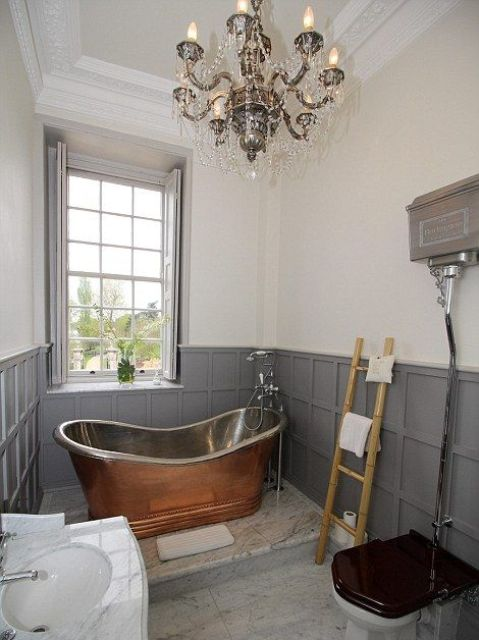a chic vintage bathroom with grey paneling, a free-standing metal tub, a crystal chandelier, a sink and a toilet