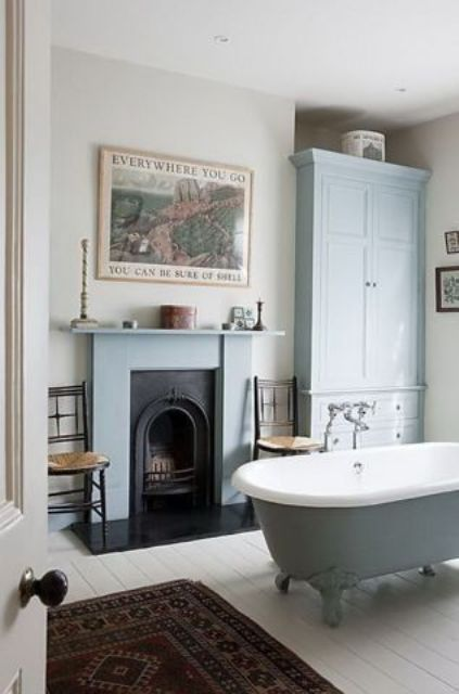 a chic vintage bathroom with powder blue furniture and a clawfoot tub, a non working fireplace, a vintage poster and a boho rug
